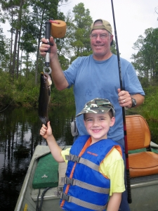 Ron Johnson holds a bowfin (mudfish) that he and his son Nathanael caught on a yellow Okefenokee Swamp Sally.