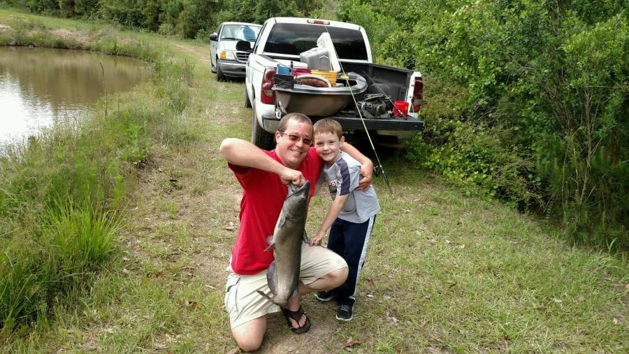 Jacob Lee (right) caught this 11.6-pound catfish last Saturday from a pond while fishing with his dad, William. Hot dog was their go-to bait. Great job, Jacob!