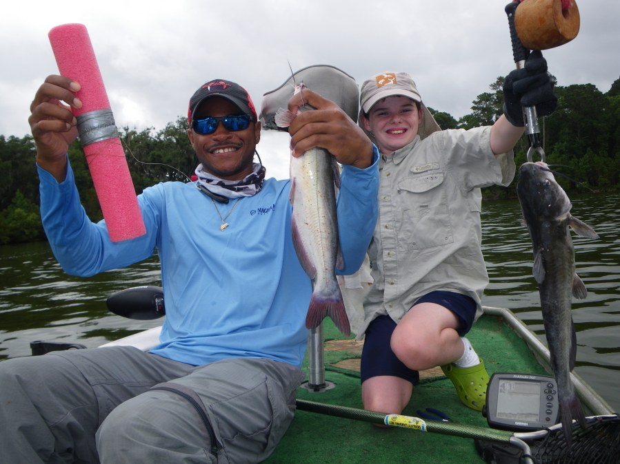 """Justin Bythwood (left) and Timothy Deener of Waycross show off two of the 36 channel catfish they caught by """"jugging"""" with pool noodles on Saturday. Their catfish ate little pieces of bluegill."""